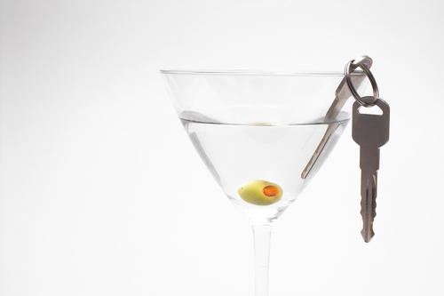 car keys hanging from a martini with an olive in it