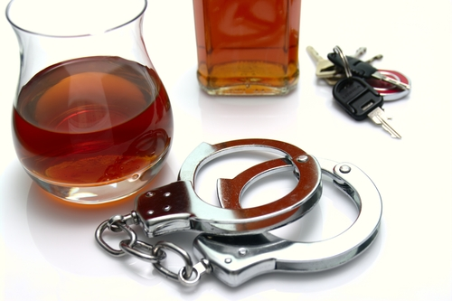 a glass of alcohol, car keys, and handcuffs on a table