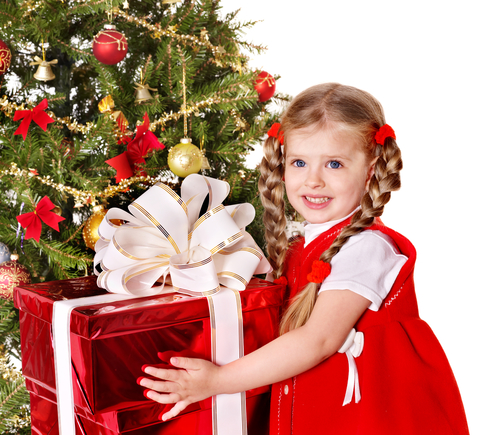 little girl in red Christmas dress holding a red gift next to the Christmas tree.