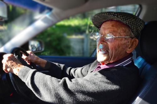 an elderly man behind the wheel of a car